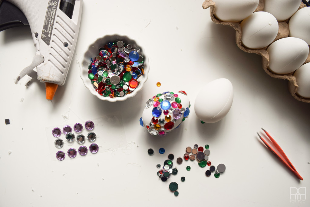 eggs with rhinestones and glue gun shown on table