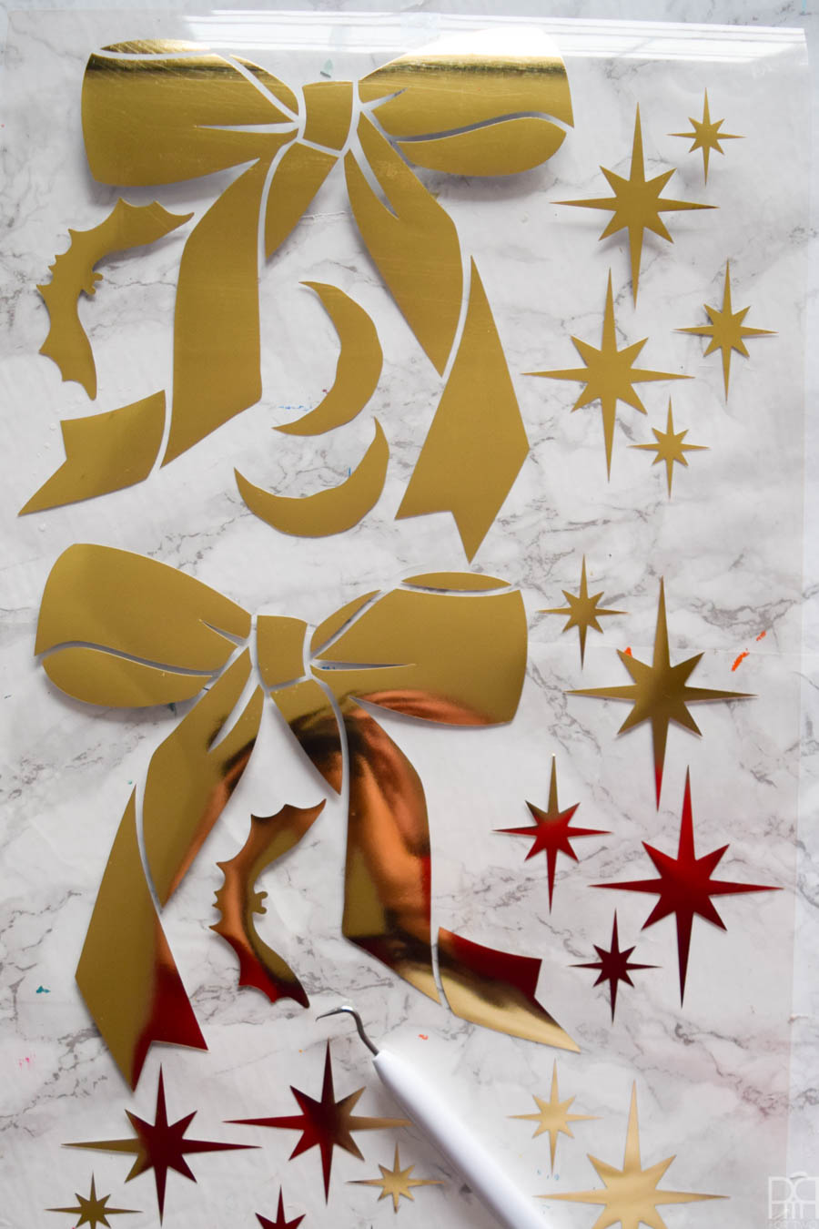 bows and atomic starbursts cut out of gold HTV against a marble background