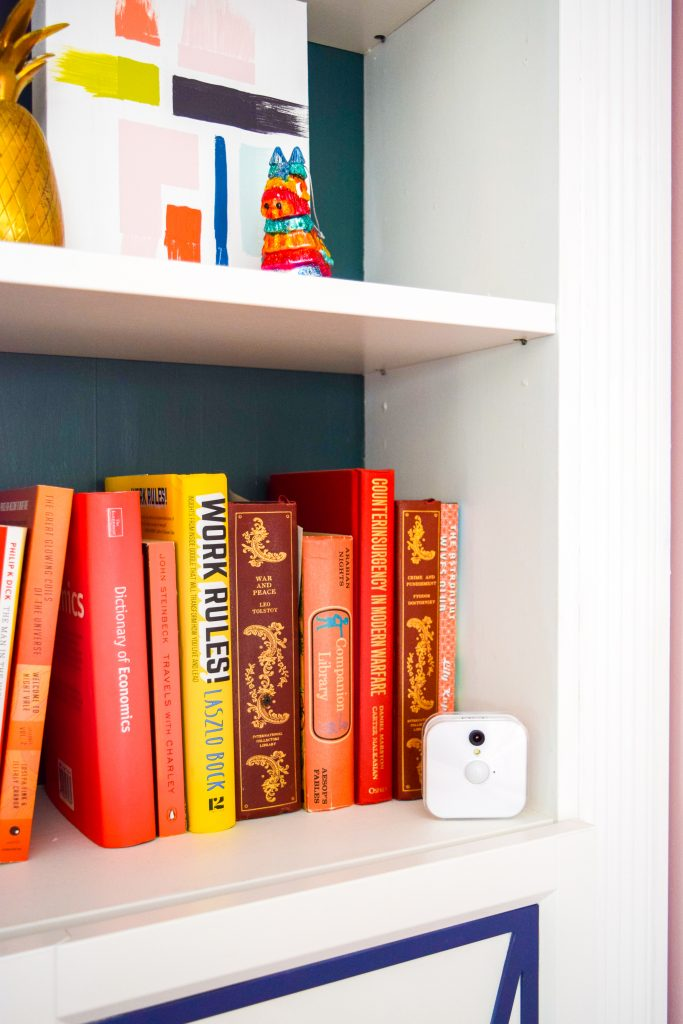 orange and yellow books on shelf with white indoor Blink security camera