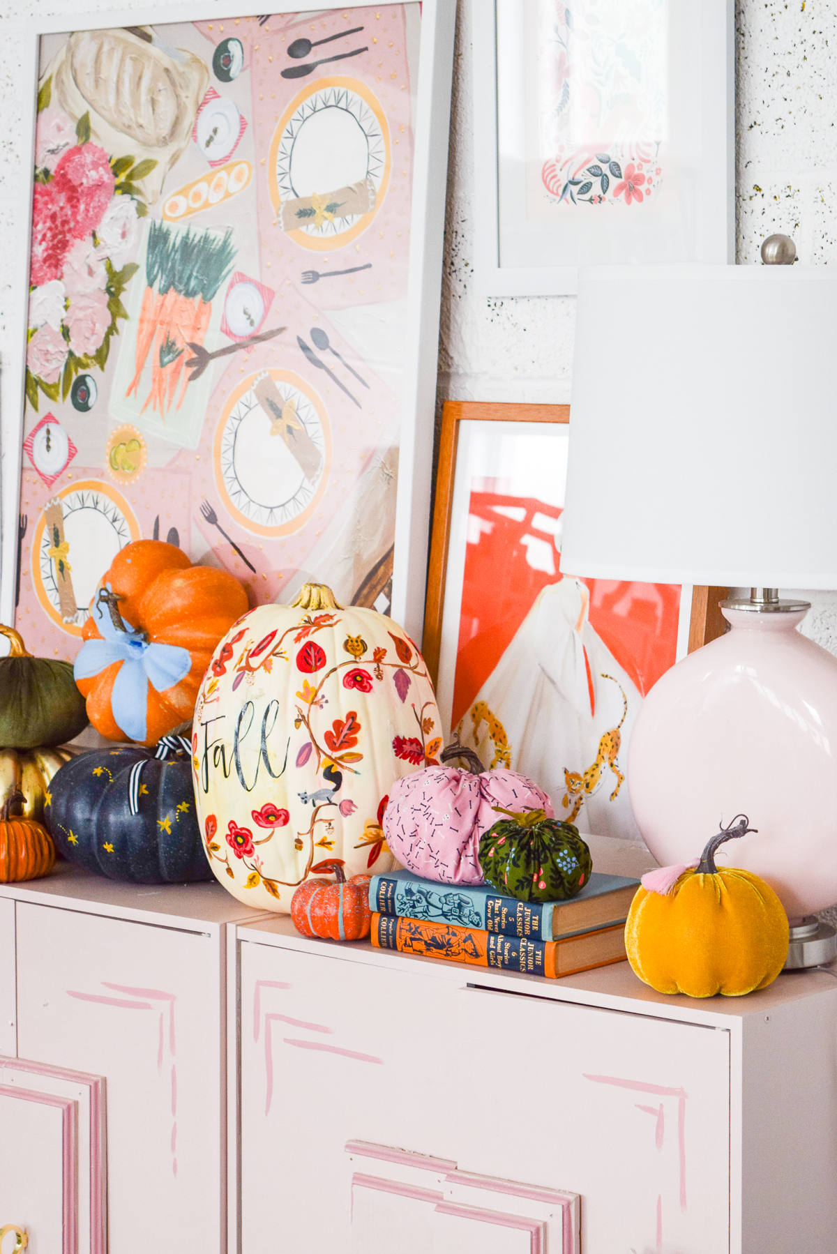 pink dresser with pumpkins and art