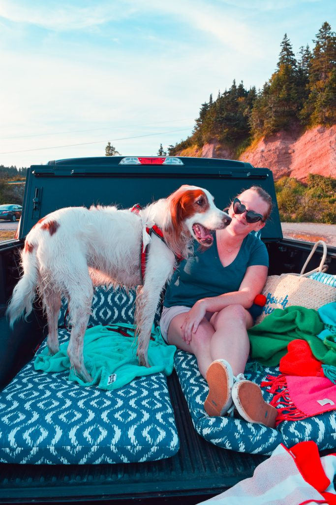 woman and dog sitting in the bed of truck