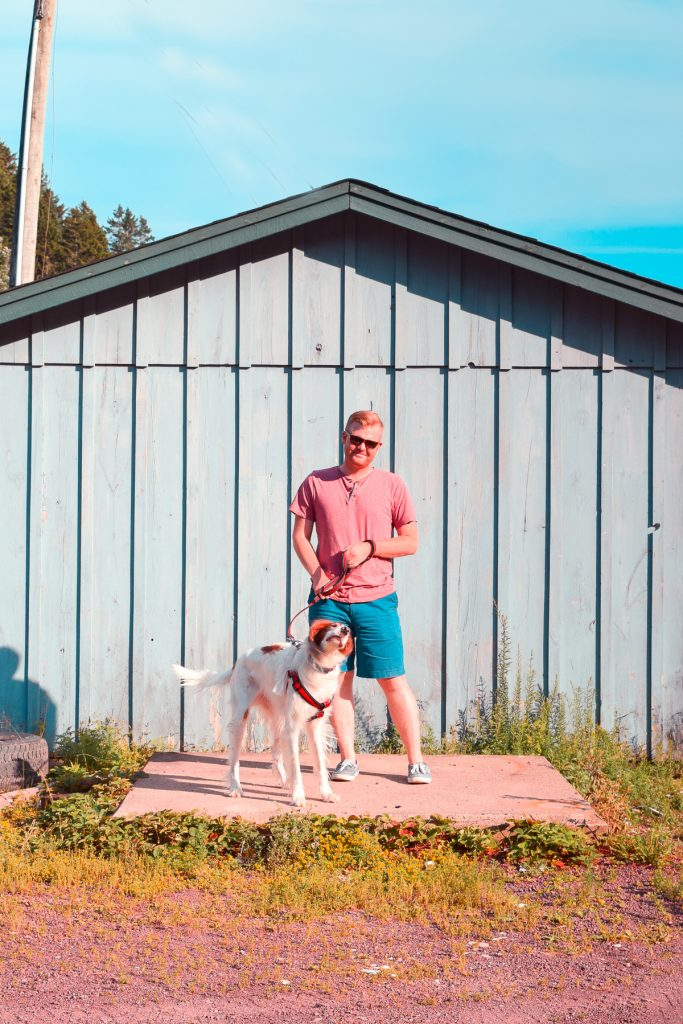 man and dog standing in front of sea shack
