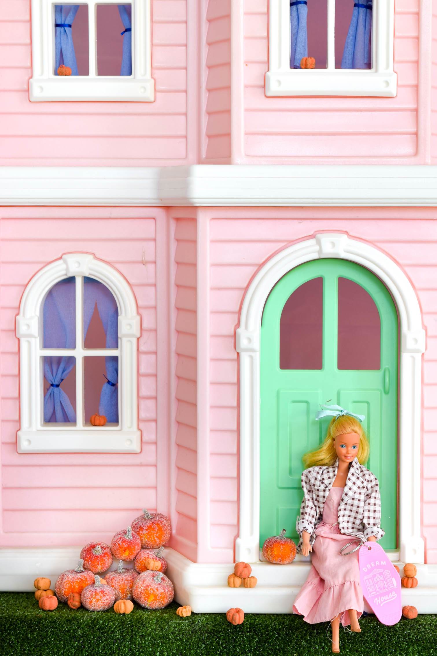 barbie doll sitting on stoop of dream house with pumpkins around