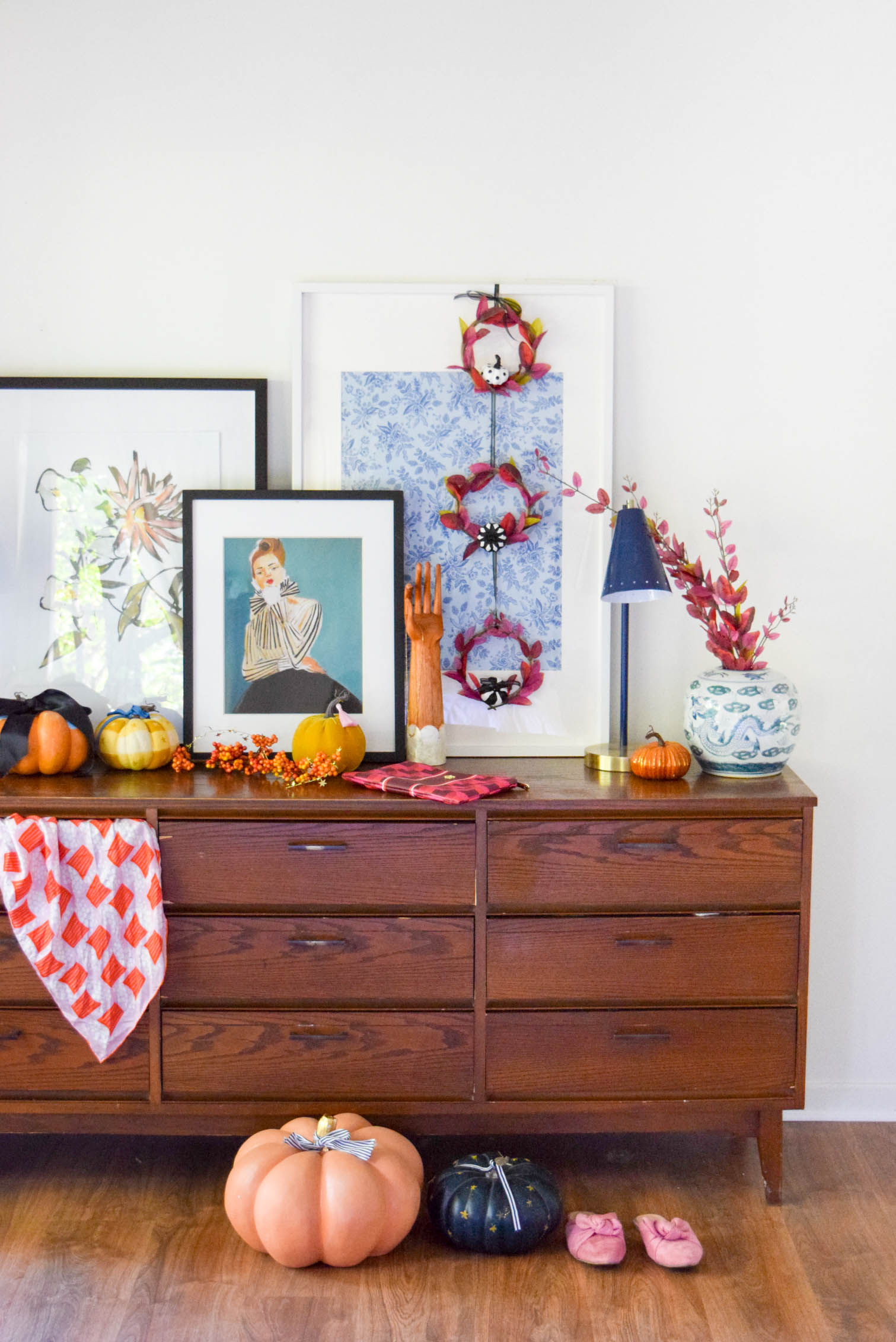 wide shot of a dresser decorated for fall with pumpkins and mini purple fall wreaths