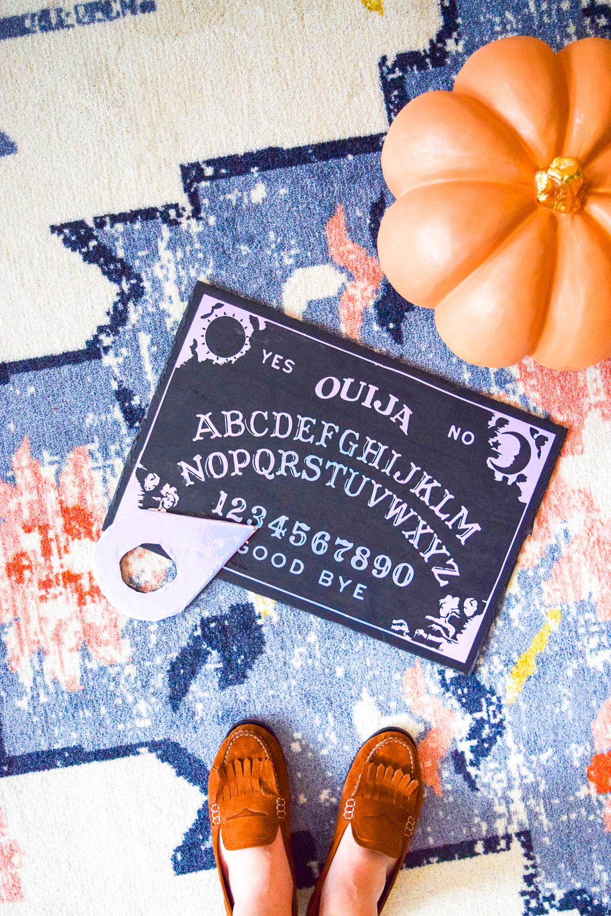 diy holographic ouija board on a carpet near a pumpkin