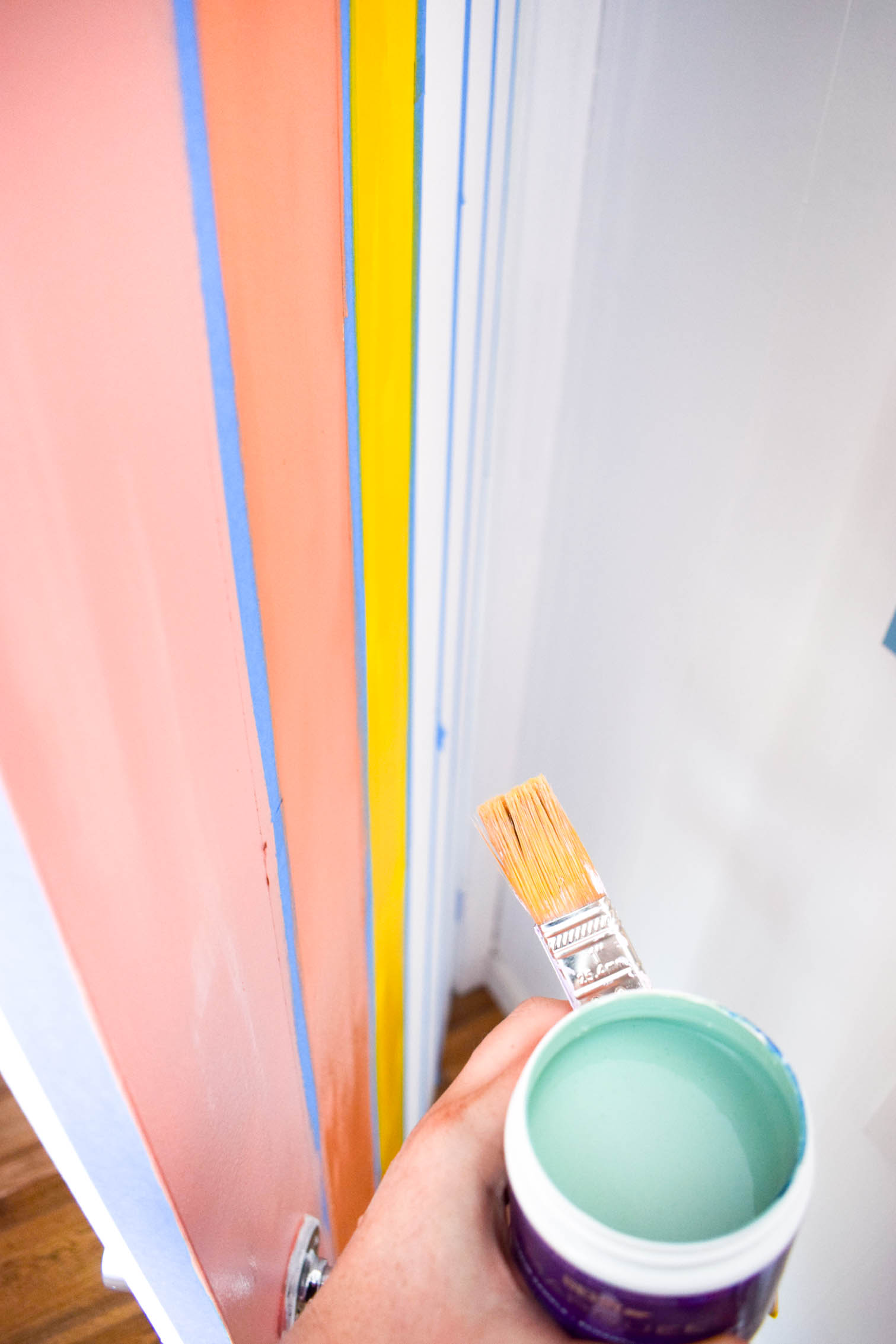 A DIY rainbow nursery door is how you nail two trends in one project! Get rainbows and murals all in one, and add a major pop of color to any space.