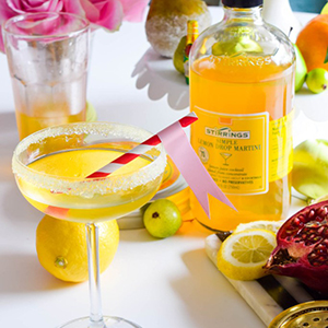 lemon drop martini shown with pink and white striped straw