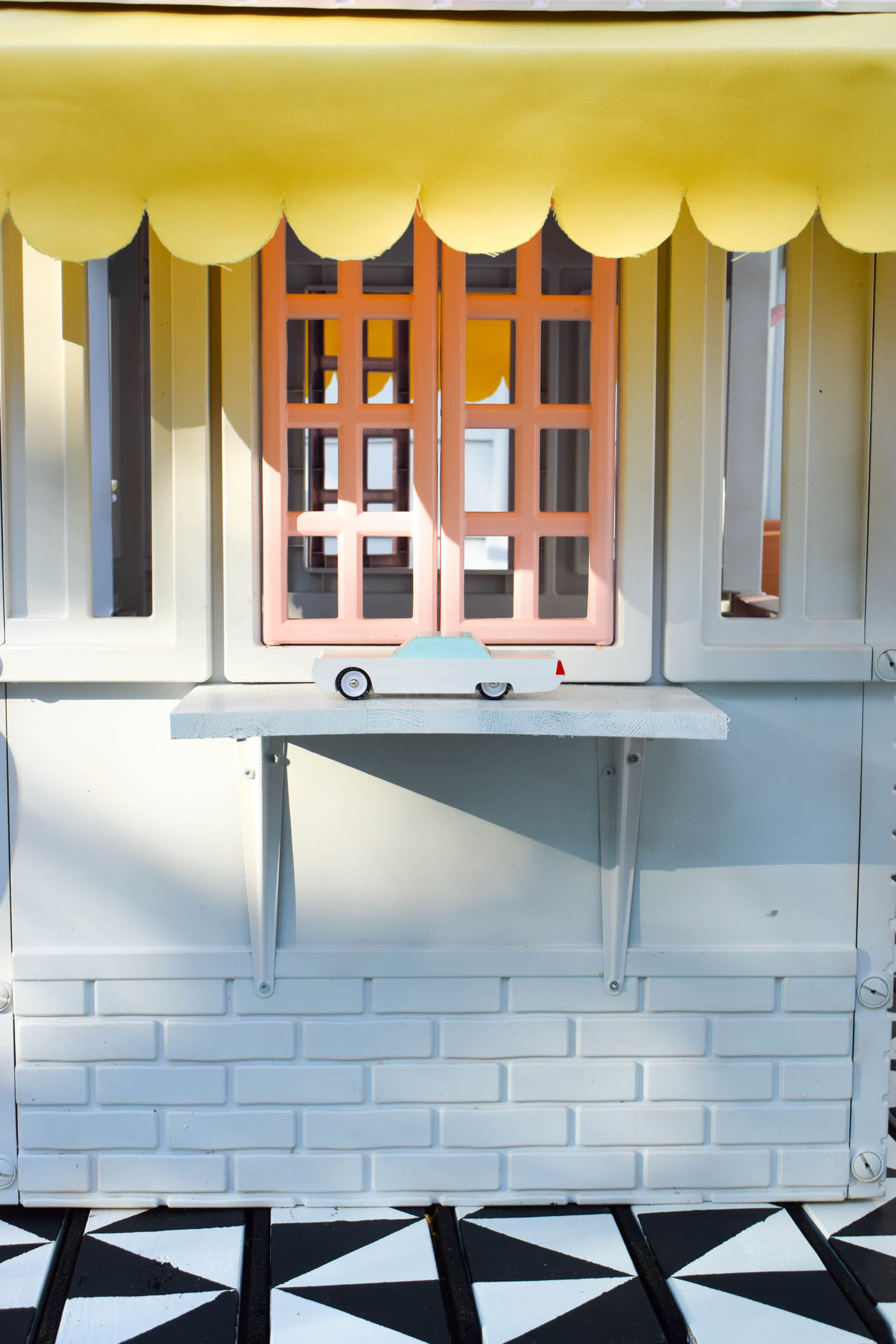 I completed a Mid Century Playhouse Makeover with a floating deck, painted to look like tiles. Easy! Come grab the tutorial and see the pics.